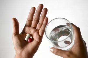 photo de mains avec des pilules mal de dos